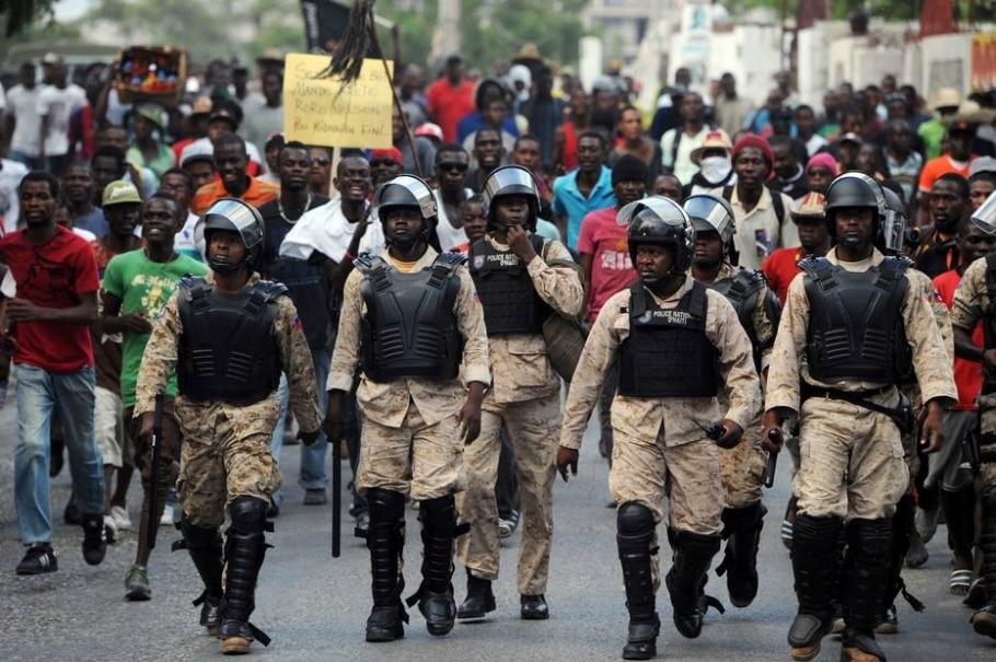 Policiais haitianos acompanham manifestação de opositores que pedem novas eleições -  AFP / HECTOR RETAMAL