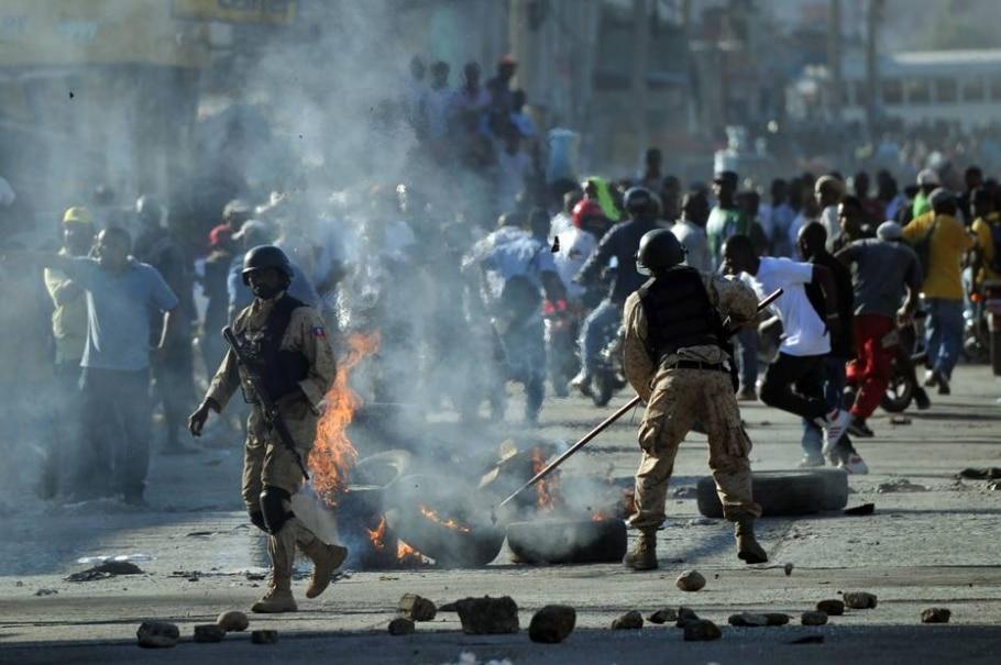 Policiais haitianos tentam dispersar manifestação e desmontar barricadas durante protesto na capital Porto Príncipe - AFP / HECTOR RETAMAL