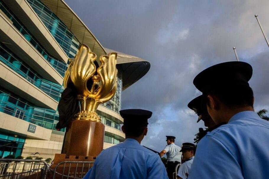 Policiais de Hong Kong retiram pano usado por ativistas anti-China para cobrir a estátua Golden Bauhinia em protesto antes da visita do líder chinês Xi Jinping - AFP PHOTO / Anthony WALLACE