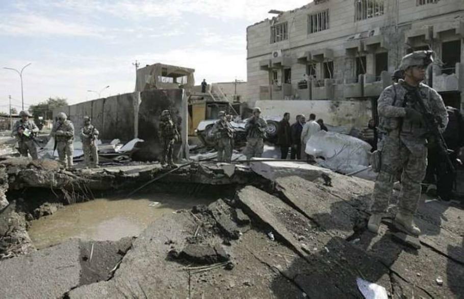 Militares americanos em guarda junto ao buraco feito por um ataque de bomba em Baghdad - Saad Shalash/Reuters
