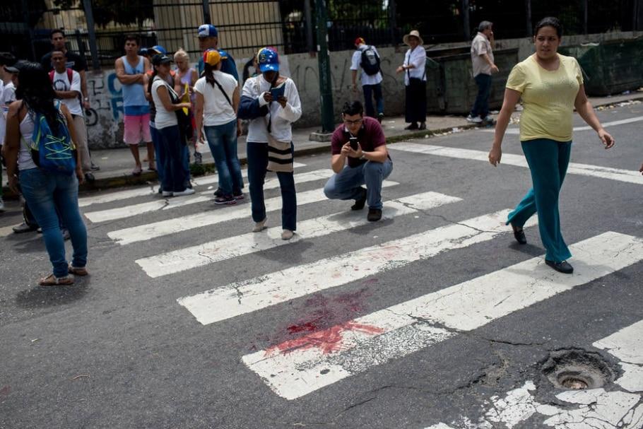 Venezuelanos fotografam mancha de sangue no local em que o jovem de 17 anos foi baleado e morto durante protestos contra Nicolás Maduro - EFE/Manaure Quintero