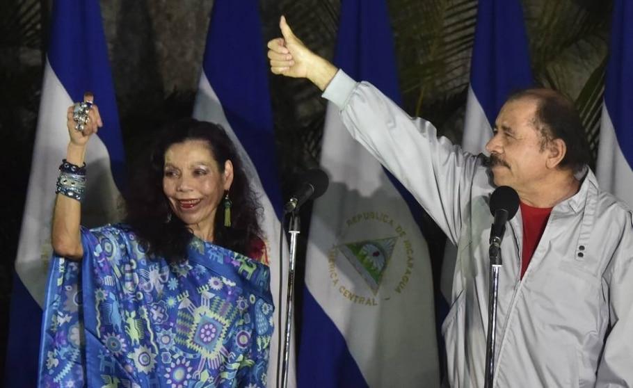 O presidente Daniel Ortega (D) e sua mulher e candidata à vice, Rosario Murillo, acenam depois de votar; casal deve ser eleito com folga - AFP