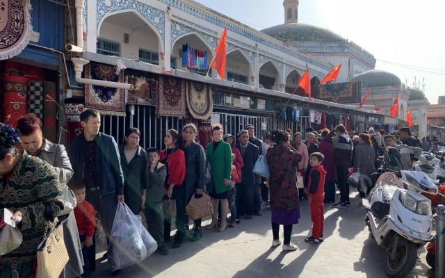 Cidadãos em Kashgar, na região deXinjiang, fazem fila para passarem por ponto de identificação