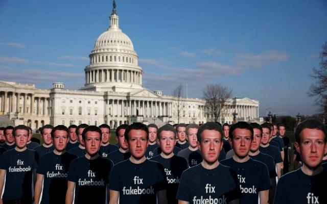 """Cartazes com a foto de Mark Zuckerberg e a instrução """"consertem o Fakebook"""" fizeram parte de protestos contra rede social, na época dos depoimentos de Zuckerberg ao Congresso americano"""