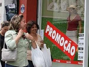 Márcio Fernandes/Estadão - Cartazes em vitrines tentam atrair consumidor para dentro da loja