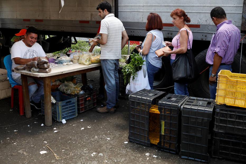 Venezuelanos compram vegetais em barraca de feirante na capital Caracas; inflação recorde corrói poder de compra no país
