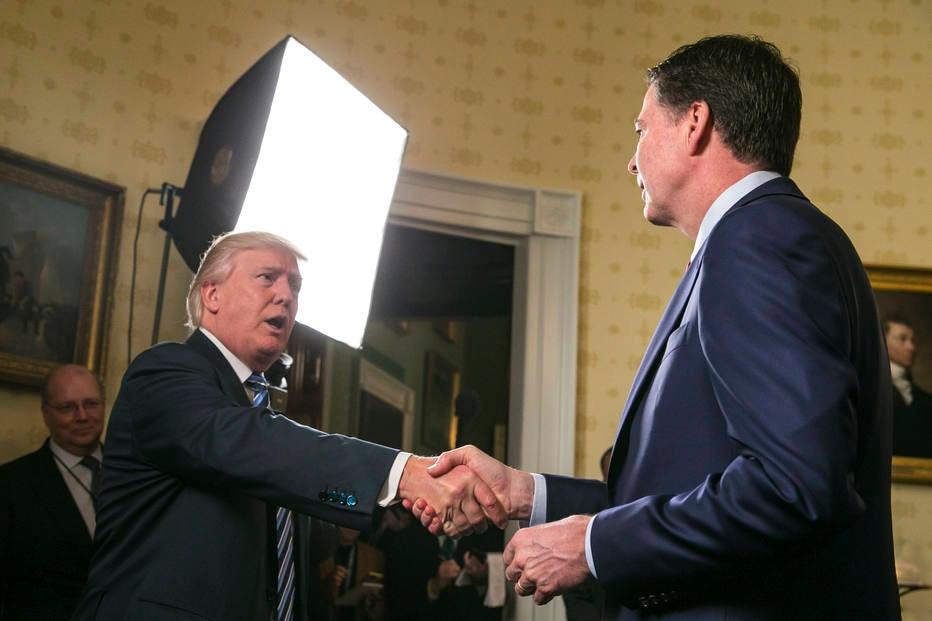 Trump cumprimenta o então diretor do FBI, James Comey, em recepção na Casa Branca em 22 de janeiro, dois dias após a posse do republicano