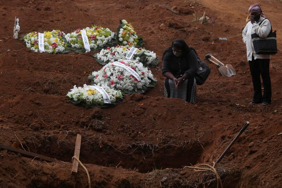 Madalena Cruz da Silva enxuga as lágrimas perto de sua filha Vera Lucia logo após o enterro de seu filho, Paulo Roberto Cruz da Silva, 47 anos, que morreu da doença por coronavírus (COVID-19), no cemitério São Luiz, em São Paulo.