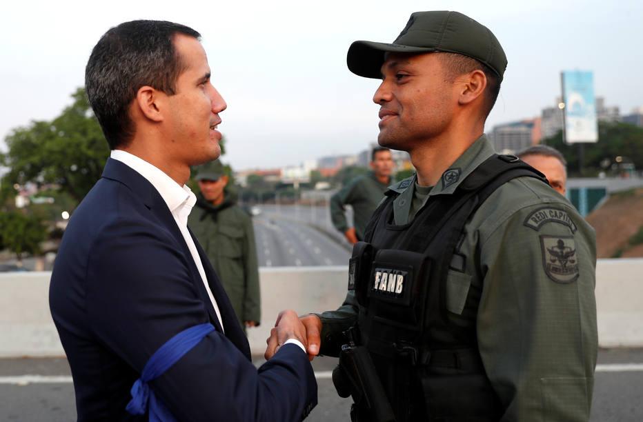 Líder opositor venezuelano, Juan Guaidó, cumprimenta  militar perto da base aérea La Carlota, em Caracas; ele diz ter apoio de militares contra Maduro