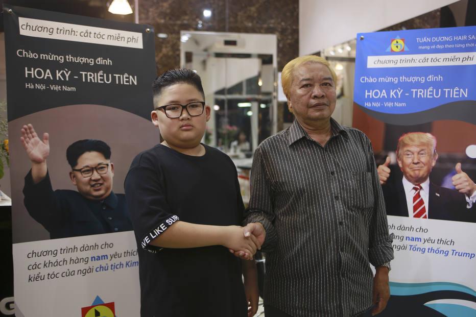 To Gia Huy, de 9 anos, e Le Phuc Hai, de 66 anos, se cumprimentam depois de mudarem os cortes de cabelo para o estilo de Kim e Trump, respectivamente
