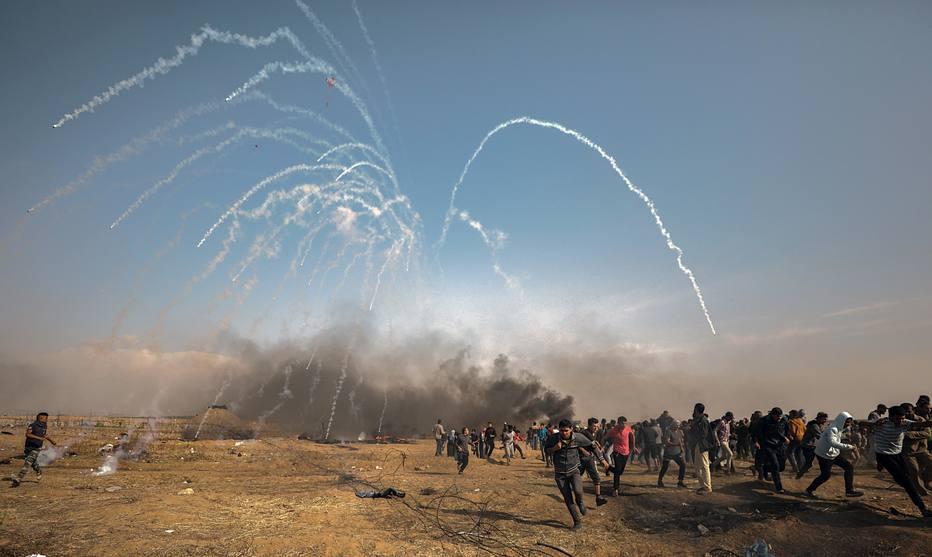 Palestinos fogem da fronteira da Faixa de Gaza depois de as forças de Israel lançarem bombas de gás lacrimogêneo contra os manifestantes