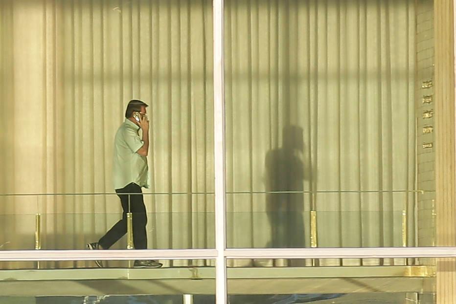 O presidente da Republica, Jair Bolsonaro fala ao telefone ao caminhar da biblioteca para area dos aposentos, no salao principal do Palacio da Alvorada.