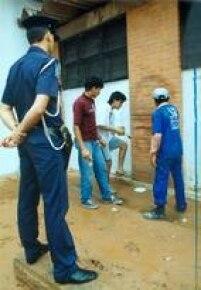 Neto e Binho, os dois rapazes que picharam o Cristo Redentor no Rio de Janeiro, limpam as paredes de um posto de assistência médica como pena do vandalismo.