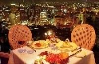 Mesa de jantar do restaurante Terraço Itália, no Edifício Itália, com vista noturna da região central da capital paulista.