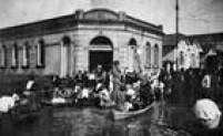 Moradores são transportados em barcos, próximo ao embarcadouro da rua Anhaia, duranteenchenteem São Paulo, década de 1920.