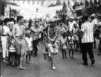 Foliões fantasiados dançam e se divertem no carnaval de rua, ao centro um passista, observado por um garoto, Rio de Janeiro, 1963
