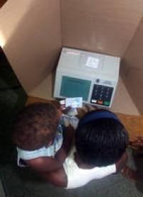 Eleitora, com criança no colo, durante votação utilizando a urna eletrônica, em São Luis, no Maranhão, 06/10/2002.