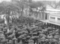 Público aguarda abertura dos portões do hipódromo do Jockey Club de São Paulo, debaixo de chuva para adentrar ao recinto e acompanhar as corridas do dia. São Paulo, SP, 13/9/1958.