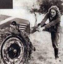 Trabalhadora limpa lama da roda de um trator. Mulheres tomaram conta da produção agrícola na Europa, durante a Segunda Guerra Mundial, 1940.
