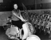 """Mulher dirige uma motocicleta Lambretta na fábrica """"Lambretta do Brasil S.A."""", no bairro da Lapa, na zona oeste de São Paulo, 11/10/1956."""