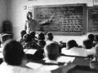 No Grupo Escola de Vila Nova professora usa régua na lousa na sala do 1.º ano B masculino. Foto 1966