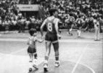 """O jogador de basquete Hélio Rubens entra na quadra segurando a mão de seu filho """"Helinho"""",São Paulo, SP, 04/02/1981."""