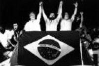 O candidato à Presidência<a href='http://https://acervo.estadao.com.br/noticias/personalidades,lula,470,0.htm' target='_blank'>Luiz Inácio Lula da Silva</a>(PT)de mãosdadas com os ex-candidatos ao Planalto,<a href='http://https://acervo.estadao.com.br/noticias/personalidades,mario-covas,1009,0.htm' target='_blank'>Mário Covas</a>(PSDB) e<a href='http://https://acervo.estadao.com.br/noticias/personalidades,leonel-brizola,720,0.htm' target='_blank'>Leonel Brizola</a>(PTB), durante comício de campanha no segundo turno das eleições presidenciais. O evento foi realizado na capital do Rio.Rio de Janeiro, RJ. 13/12/1989.