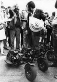 Jânio coça a cabeça enquanto ouve explicações sobre o funcionamento dos<a href='http://https://acervo.estadao.com.br/noticias/acervo,walk-machine-o-avo-do-patinete,70002842198,0.htm' target='_blank'>walk-machines</a>, 01/7/1988. Foto: César Diniz/ Estadão