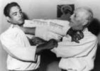 Rickson Gracie, lutador de jiu-jitsu e pioneiro do<a href='http://https://acervo.estadao.com.br/noticias/acervo,primordios-do-vale-tudo-e-mma-jiu-jitsu-x-capoeira,9298,0.htm' target='_blank'>MMA</a>, e seu pai, o lendário Hélio Gracie em 23 janeiro 1989