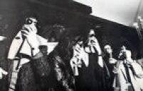 Integrantes do Kiss, sem sua caracterização, usam óculos escuros e cobrem os rostos durante entrevista, 24/6/1983