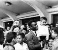 Pelésegura menino no colo, ao ser recepcionado por torcedores no Aeroporto de Congonhas, depois de uma partida pela Seleção Brasileira.São Paulo, SP, 08/7/1965.