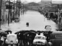 Veículos e pedestres enfrentam enchente na Rua do Gasômetro, no Brás, em São Paulo.SP. 17/3/1966.
