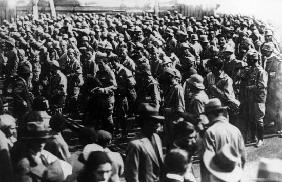 Soldados atravessam a cidade em direção aos trens que se dirigem ao fronte, São Paulo, SP, 1932.