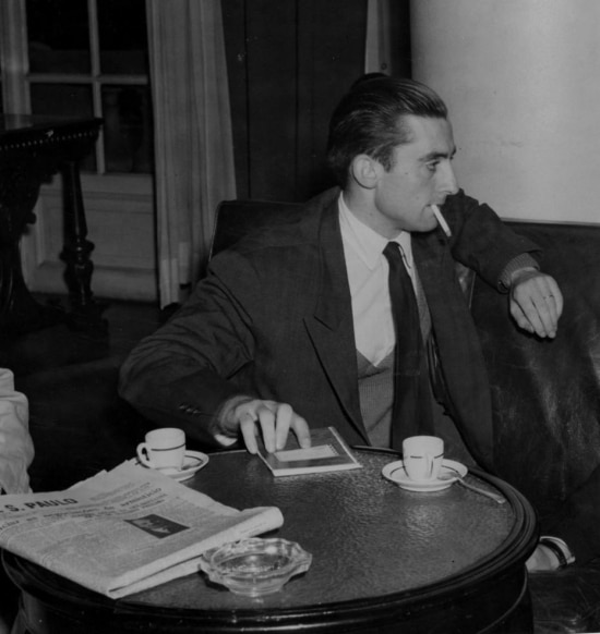 Gilles Lapouge fuma um cigarro apóslerum exemplar do Estadão, 1958.