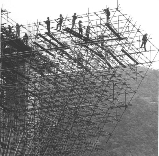 Operários trabalhando sobre andaimes na construção da Rodovia dos Imigrantes. A Rodovia dos Imigrantes tem 44 viadutos, sete pontes e onze túneis, em 58,5 km de extensão, de São Paulo até Praia Grande, no litoral Sul do estado. É a principal via de acesso da cidade de São Paulo à Baixada Santista, 18/4/1974.