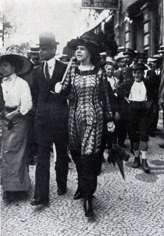 Mulher usando jupe-culotte atrai a atenção de curiosos no Rio de Janeiro no início do século 20. Revista Careta, 1911