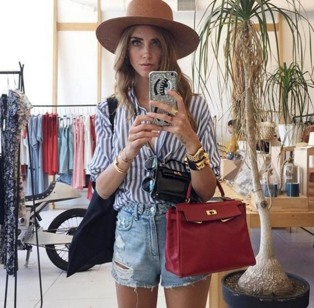A blogueira italiana Chiara Ferragni é adepta da febre de usar duas bolsas no mesmo look. Na foto, ela exibe a versão tradicional e miniatura da bolsa Kelly, da Hermès