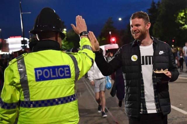 Na saída do show One Love Manchester, homem cumprimenta um policial.