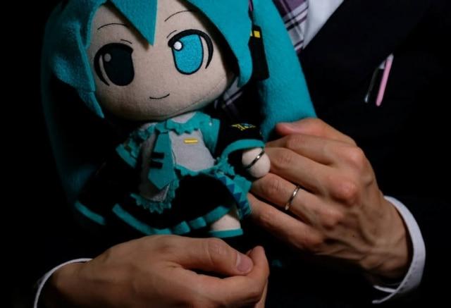 Akihiko Kondo mostra as alianças trocadas com a boneca.