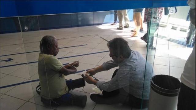 O gerente de uma agência da Caixa Econômica Federal sentou-se no chão para atender um cliente.