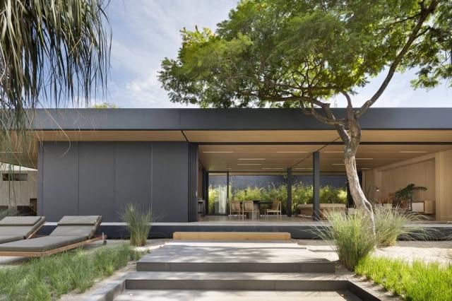 A fachada principal da Syshaus, com amplas aberturas para o jardim externo Tempo, projetado por Renata Tilli, Vera Oliveira e Lucas Tell Push