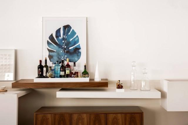 Prateleira fixa na parede serve de apoio para bar elaborado por Guta Louro