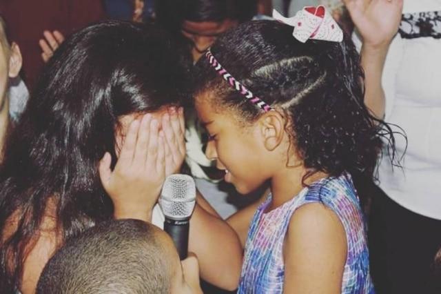 Vitória emociona devota durante oração.