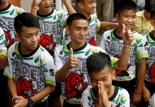 Jogadores dos 'Javalis Selvagens'e seu treinador chegam em Chiang Rai, Tailândia, para coletiva de imprensa.