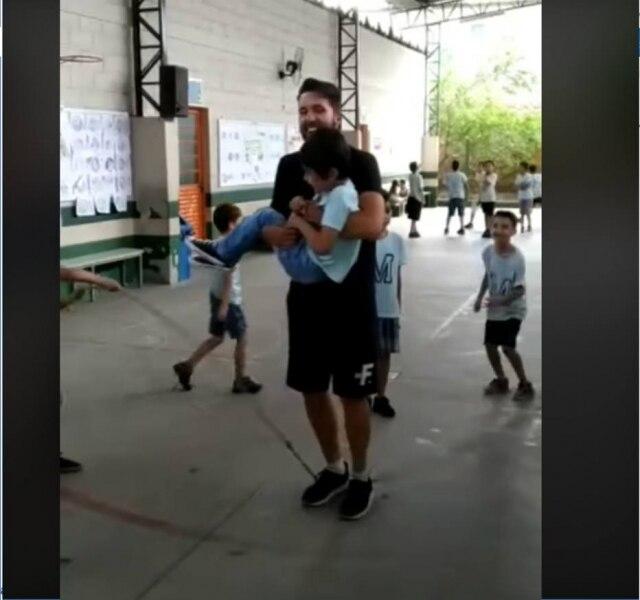 Professor carrega aluno cadeirante no colo enquanto os dois pulam corda