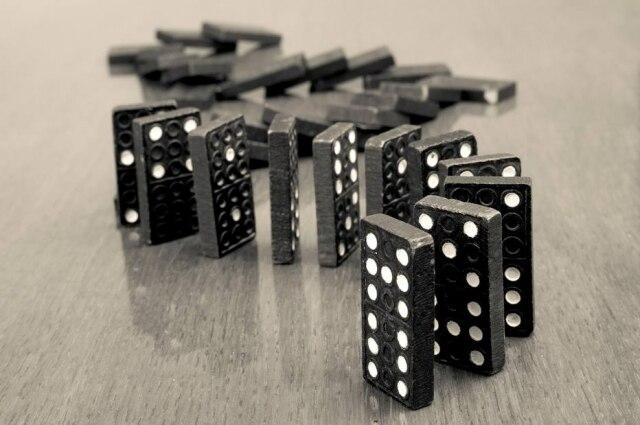 Jovem monta dominós em cadeia, criando imagens e efeitos hipnóticos.