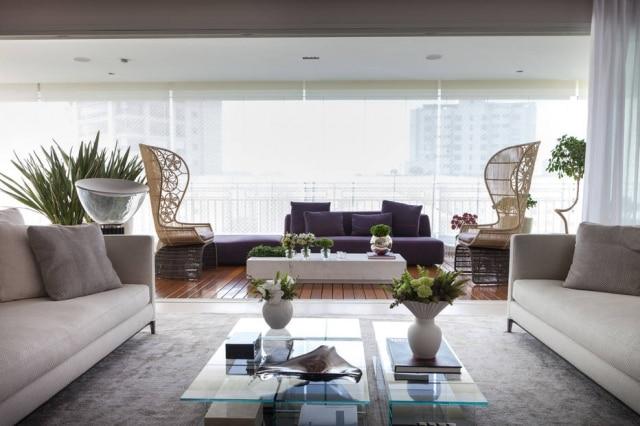 Com projeto de Olegario de Sá e Gilberto Cioni, a varanda tem sofá roxo e poltronas de fibra natural