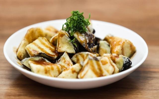 Berinjela no missô com shoyu, ela vem em pedaços médios, é empanada e frita. Chega sequinha, macia, levemente adocicada pelo molho.