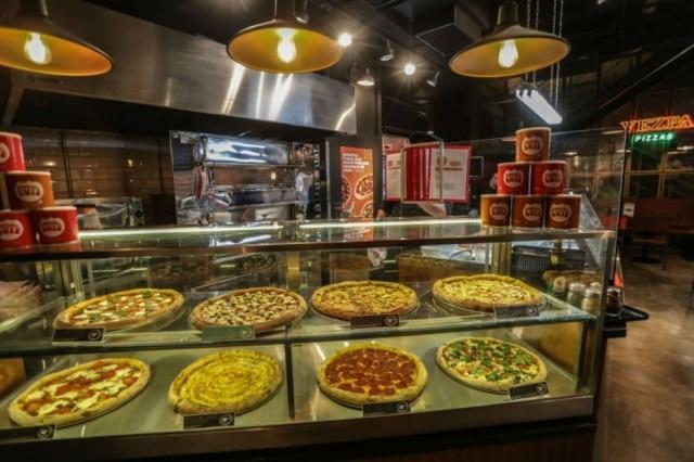Informal. Os discos ficam dispostos no balcão, a proposta da Vezpa é servir pizzas por fatia a qualquer hora do dia, rápido e descomplicado