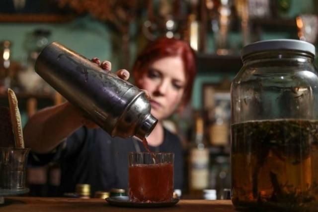 Neli prepara o drinque Levante, com garrafada de catuaba e ervas que faz na casa